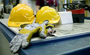 Zwei gelbe Bauarbeiterhelme und ein Handschuh